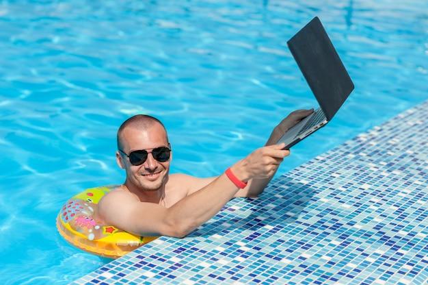 Młody człowiek na wakacjach z laptopem, biznes online. odległość biura domowego w basenie w gumowym pierścieniu na kwarantannie