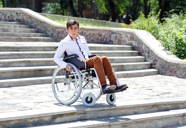 Młody człowiek na wózku inwalidzkim, który nie może zejść po schodach.