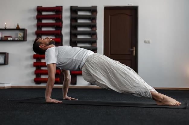 Młody człowiek na zajęciach jogi w studio fitness.