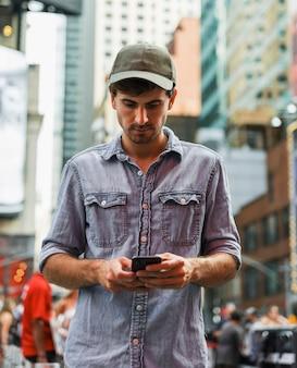 Młody człowiek na zewnątrz przy użyciu telefonu