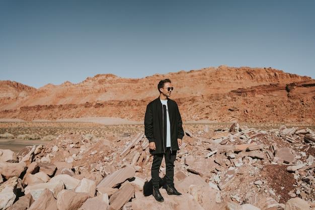 Młody człowiek na zewnątrz w sunglases cieszący się słońcem w czerwonych górach arizony