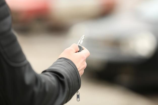 Młody człowiek na zewnątrz za pomocą alarmu samochodowego
