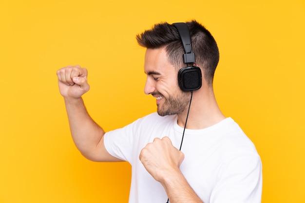 Młody człowiek na żółtej ścianie słuchania muzyki i tańca
