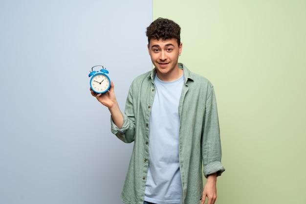 Młody człowiek nad błękitną i zieloną ścianą trzyma rocznika budzika
