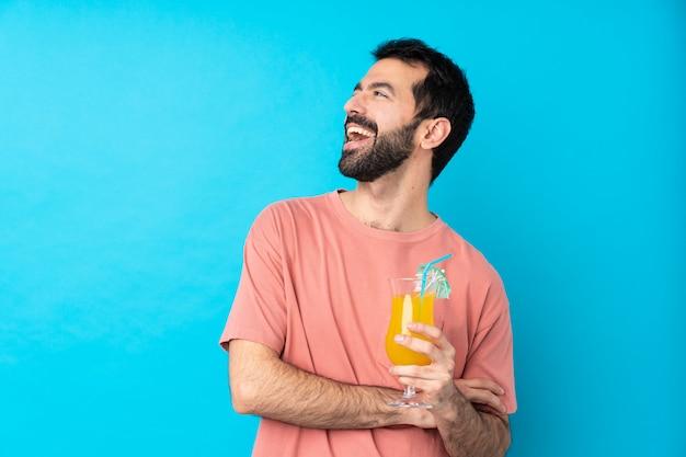 Młody człowiek nad koktajlem szczęśliwym i uśmiechniętym