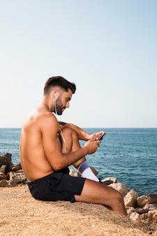 Młody człowiek nad morzem słuchania muzyki