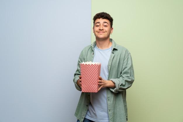 Młody człowiek nad niebieską i zieloną ścianą je popcorns