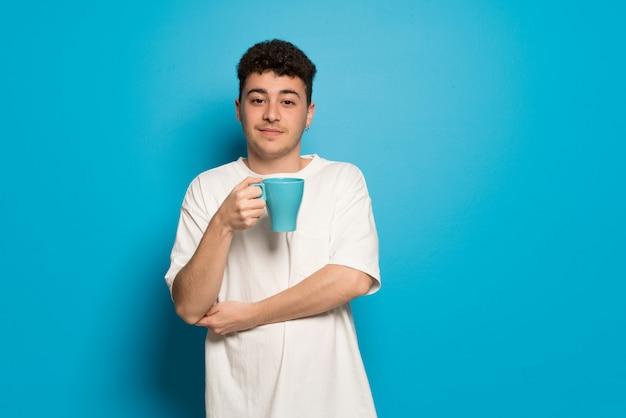 Młody człowiek nad niebieską ścianą trzyma filiżankę gorącej kawy