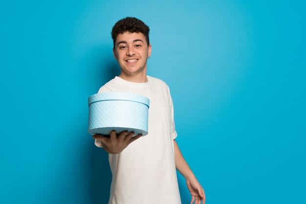 Młody człowiek nad niebieską ścianą trzyma prezent w ręce