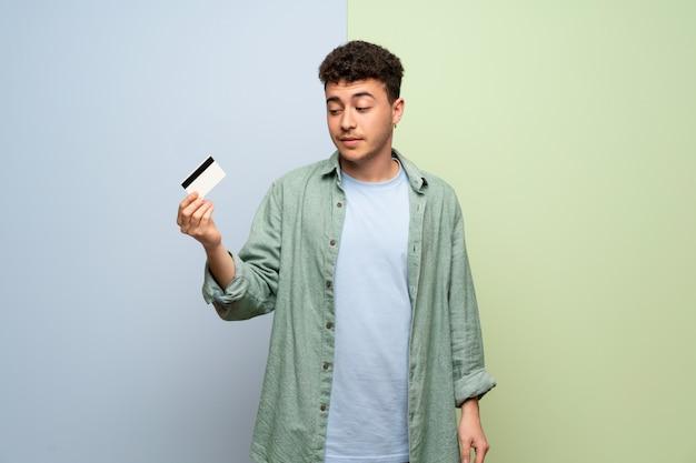 Młody człowiek nad niebieski i zielony biorąc kartę kredytową bez pieniędzy