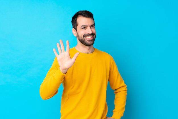 Młody człowiek nad odosobnioną błękit ścianą liczy pięć z palcami