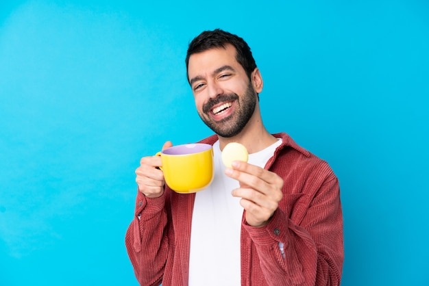 Młody człowiek nad odosobnioną błękit ścianą trzyma kolorowych francuskich macarons i filiżankę mleka