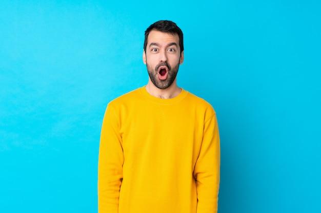 Młody człowiek nad odosobnioną błękit ścianą z niespodzianka wyrazem twarzy