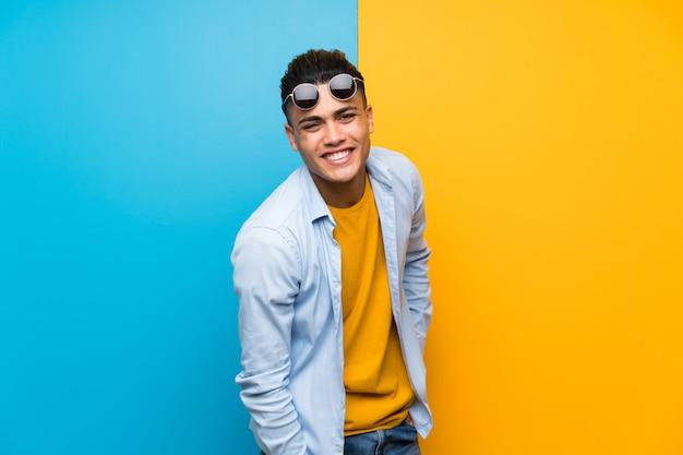 Młody człowiek nad odosobnioną kolorową ścianą z okularami przeciwsłonecznymi