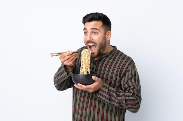 Młody człowiek nad odosobnioną ścianą trzyma puchar kluski z pałeczkami i je je
