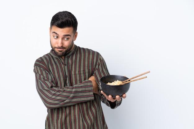 Młody człowiek nad odosobnioną ścianą z smutnym wyrażeniem podczas gdy trzymający puchar kluski z chopsticks