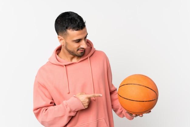 Młody człowiek nad odosobnionym bielem z piłką koszykówka i wskazywać je