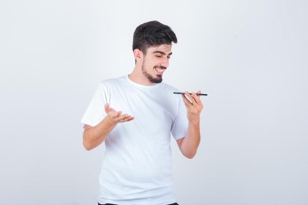Młody człowiek nagrywa wiadomość głosową na telefonie komórkowym w koszulce i wygląda na szczęśliwego