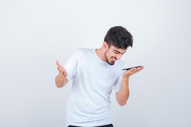 Młody człowiek nagrywa wiadomość głosową na telefonie komórkowym w koszulce i wygląda pozytywnie