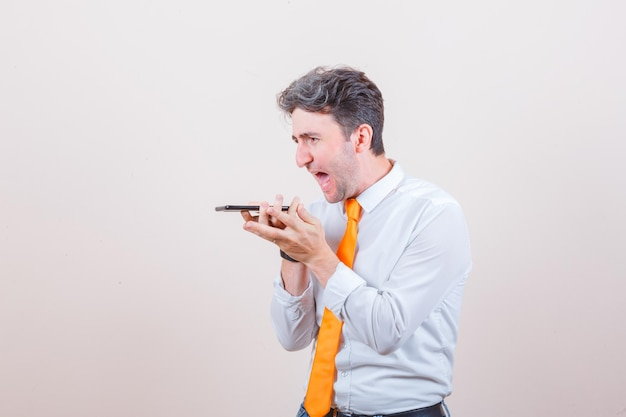 Młody człowiek nagrywa wiadomość głosową na telefonie komórkowym w koszuli i wygląda na zdenerwowanego