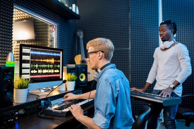 Młody człowiek nagrywanie muzyki przez komputer, podczas gdy afrykański facet gra na pianoboard w studio nagrań