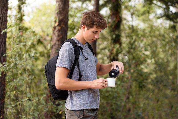 Młody człowiek nalewa napój do filiżanki