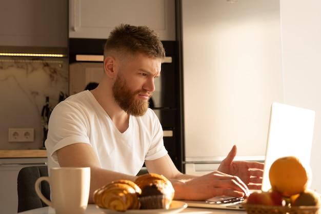 Młody człowiek napięty przy użyciu komputera przenośnego. europejski brodaty facet siedzi przy stole z pysznym jedzeniem i filiżanką z herbatą lub kawą. wnętrze kuchni w nowoczesnym mieszkaniu. słoneczny poranek