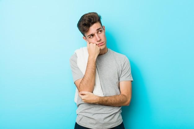 Młody człowiek nastolatek fitness, który czuje się smutny i zamyślony, patrząc na miejsce.