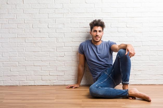 Młody człowiek naturalny siedzieć na drewnianej podłodze z rękami na biodrach, stojąc, zrelaksowany i uśmiechnięty, bardzo pozytywny i wesoły