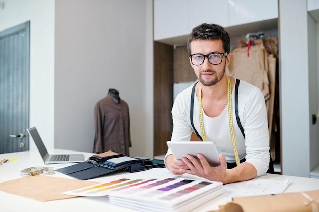 Młody człowiek nawiązuje kontakty lub surfuje po sieci w poszukiwaniu nowych, kreatywnych pomysłów na kolekcję mody, siedząc w warsztacie