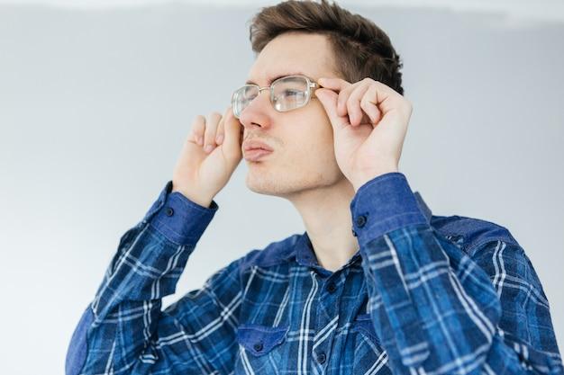 Młody człowiek niedowidzący patrzy przez okulary. mężczyzna w niebieskiej koszuli