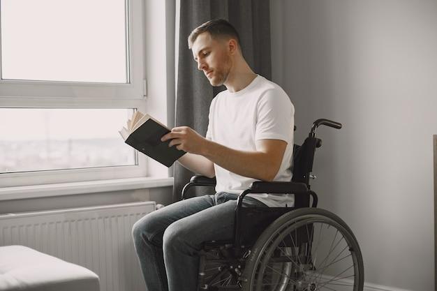 Młody człowiek niepełnosprawny. mężczyzna czyta książkę na wózku inwalidzkim, przebywa w domu.