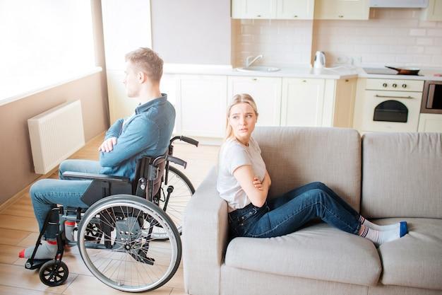 Młody człowiek niepełnosprawny siedzieć na wózku inwalidzkim i patrzeć w okno. kłócić się i walczyć. facet ze specjalnymi potrzebami siedzi tyłem do dziewczyny. młoda kobieta próbuje na niego spojrzeć.