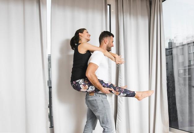 Młody człowiek niesie jej dziewczyny piggyback przejażdżkę przed zasłoną
