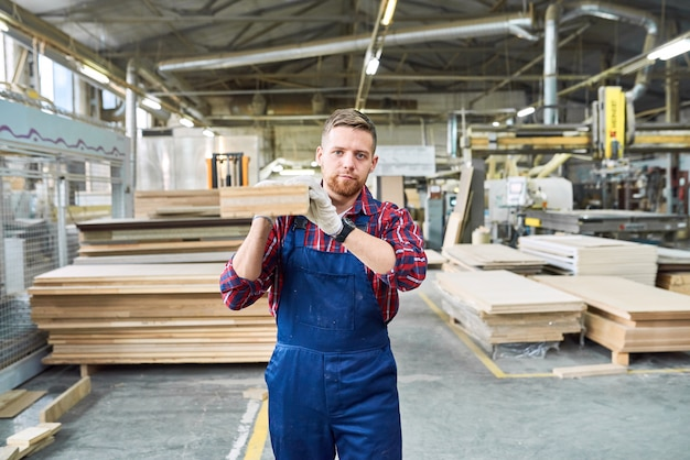 Młody człowiek niosący drewnianą deskę w fabryce