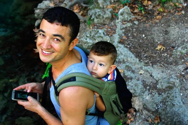 Młody człowiek niosący syna na plecach