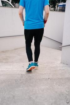 Młody człowiek nogi ćwiczy interwału trening na schodkach