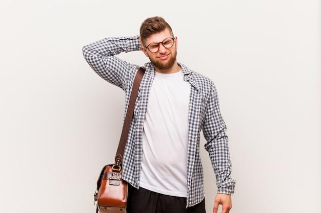 Młody człowiek nowoczesny biznes cierpi ból szyi ze względu na siedzący tryb życia.
