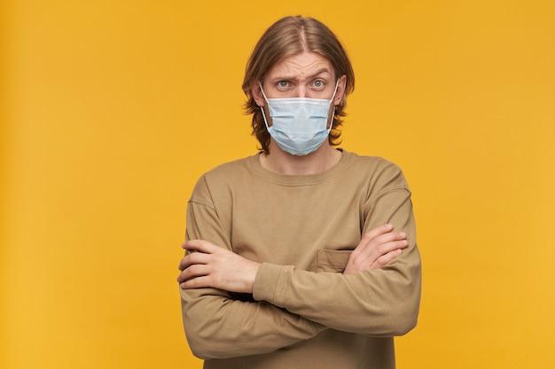 Młody człowiek o blond włosach i brodzie. noszenie beżowego swetra i medycznej maski ochronnej. trzyma ręce skrzyżowane. unosi brew. pojedynczo na żółtej ścianie