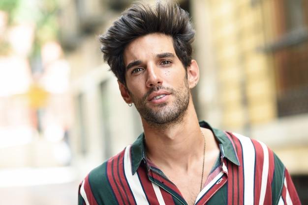 Młody człowiek o ciemnych włosach i nowoczesnej fryzurze na zewnątrz na co dzień