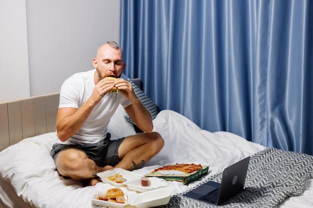Młody człowiek o fast food w domu w sypialni na łóżku