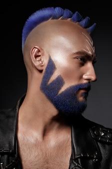 Młody człowiek o niebieskich włosach i kreatywnych makijaż i włosy.