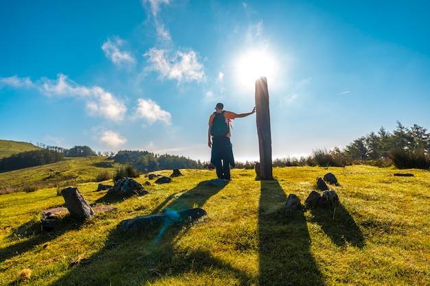 Młody człowiek o świcie obok dolmana na szczycie góry adarra w urniecie, niedaleko san sebastian. gipuzkoa, kraj basków