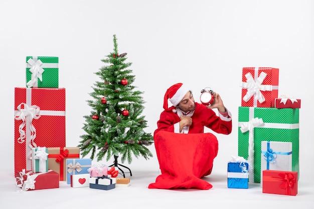 Młody człowiek obchodzi święta bożego narodzenia siedząc w ziemi i patrząc na zegar w pobliżu prezentów i ozdobione choinką