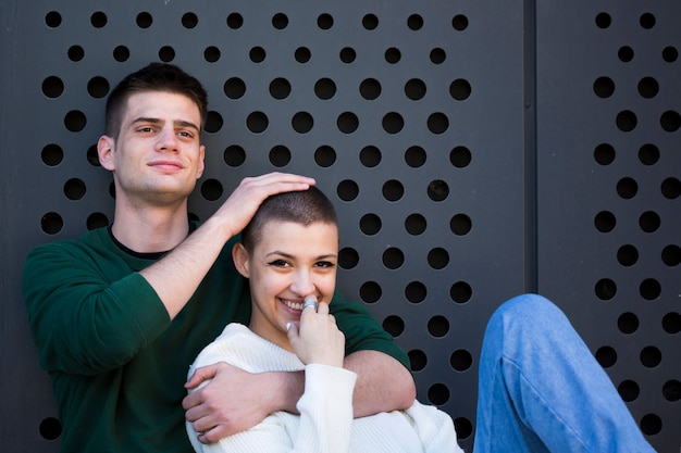 Młody człowiek obejmując szyję i dotykając głowę dziewczyny z krótkimi włosami
