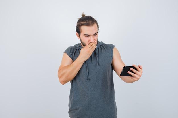 Młody człowiek obejmujący dłoń na ustach, trzymając telefon w ręku w t-shirt z kapturem i patrząc zdziwiony, widok z przodu.