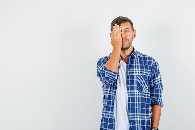 Młody człowiek obejmujący jedno oko ręką w koszuli, widok z przodu.