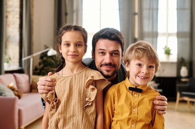 Młody człowiek obejmujący swoje dwoje uroczych małych dzieci