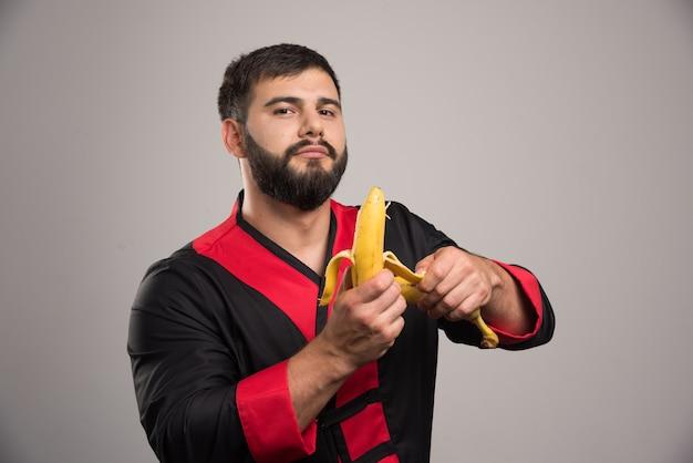 Młody człowiek obierania banana na ciemnej powierzchni.