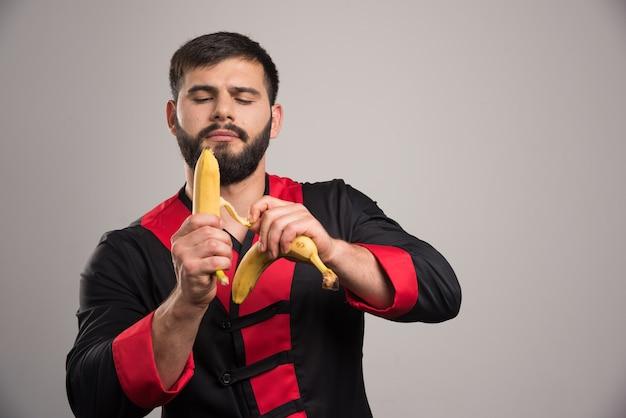 Młody człowiek obierania banana na ciemnej ścianie.